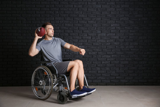 Young man with rugby ball sitting in wheelchair against dark brick wall