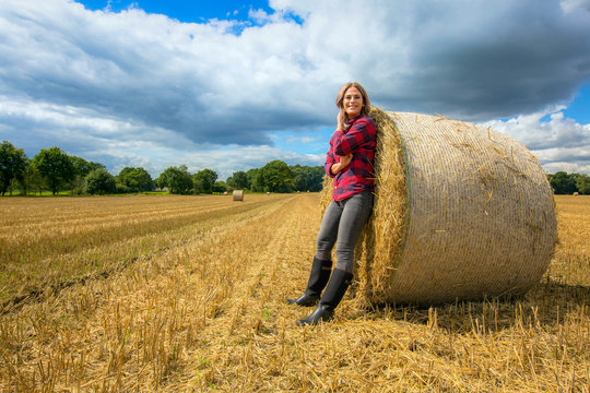 Young woman leans proudly on a straw bale
