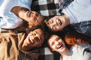 Portrait of happy people men and women laughing, and lying on blanket in circle outdoor