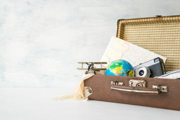 Travel, adventure, vacation concept. Brown retro suitcase with traveler set of travel booklets, maps, camera, clothes and toy plane. How to Pack a Suitcase. Explore: Adventure Travel Holidays
