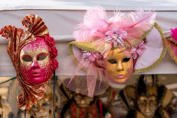 two gilded Venetian masks with feathers, with the addition of red and pink color