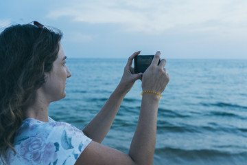 A girl on the beach with a mobile phone takes pictures of the sea.