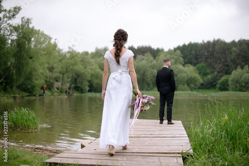 3944b3dd6d80b9 Rear view of young bride woman in beautiful white wedding dress walking to  the groom on the pier near the lake. Wedding day.