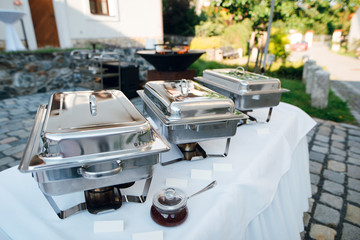 Wedding buffet table with row of hot food service steam pans. Outdoors in the garden