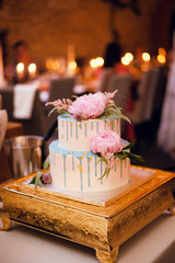 Beautiful white wedding cake with pink peony flowers standing on the golden stand in the restaurant. Delicious cake. Wedding concept