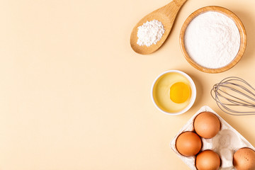 Ingredients and utensils for baking on a pastel background.