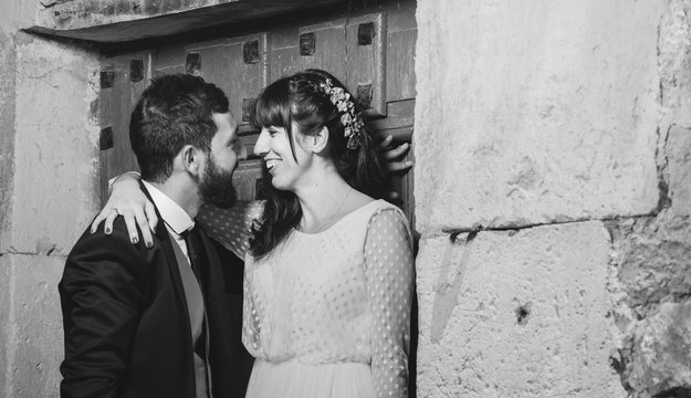Young bride and groom standing together near wall
