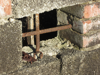 Basement window with rusty iron bars on old abandoned brick house