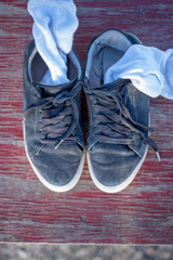 old worn tennis shoes and white socks morning sunlight