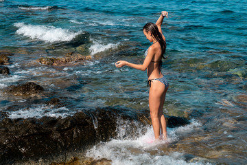 Slim young lady swims at the sea