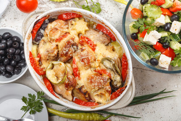 Traditional tasty rustic stew of chicken and vegetables  with Greek salad and black olives
