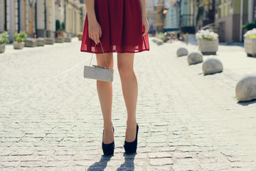 Beautiful young girl in red evening dress with bag in hands waiting for somebody in the street. Close up photo of woman's long legs in black  high-heels