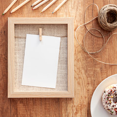 Autumnal mockup with wooden frame, colorful sprinkle donut, natural string and crayons