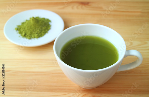 One Cup Of Vibrant Color Hot Matcha Green Tea With Blurred Powder In Background