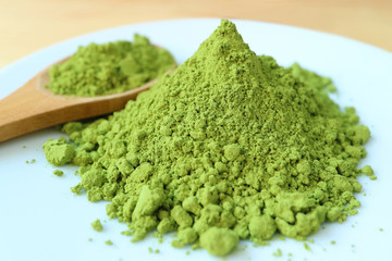 Close Up of Vibrant Green Color Matcha Tea Powder, Ingredient for Making Hot Green Tea with Blurred Wooden Spoon in Background