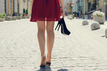 Woman in red dress, with high heel shoes in hand, walking in the city barefoot; close up photo of woman's legs, city on the background, view from back