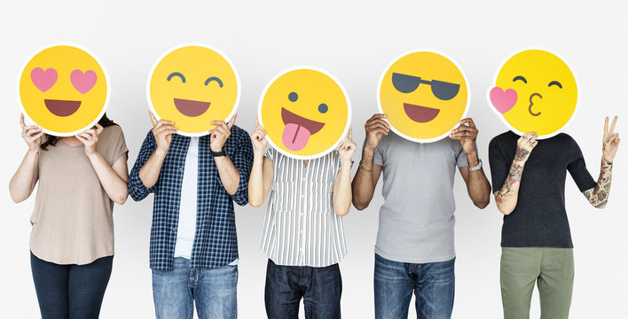 Diverse people holding happy emoticons