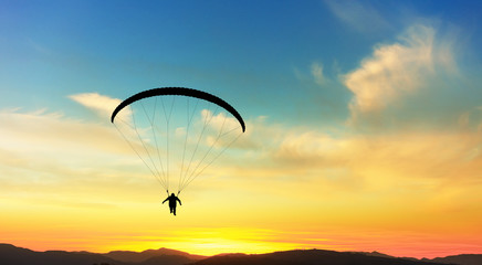 Paragliding in clouds at sunset.