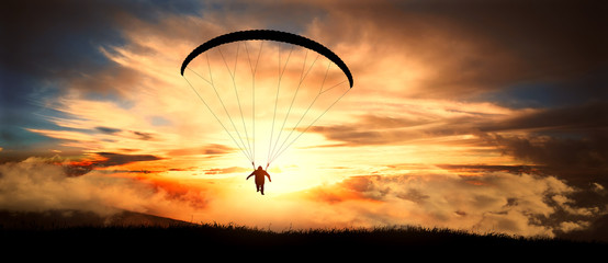 Foto auf Acrylglas Luftsport Paragliding in clouds at sunset.
