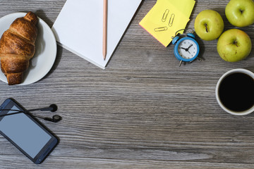 A background of office accessorise. Notepad, cup of coffee, smartphone, earphones, croissant