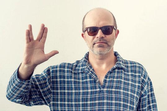 Portrait of an adult man with a gray beard, dark glasses shirt showing a gesture Star Trek, planet Vulcan