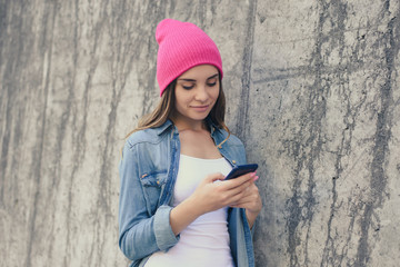 Smiling woman dressed in casual clothes and pink hat leaning on the street wall and using internet for chatting