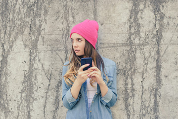 Jealous woman checking her boyfriend's mobile phone. Woman reading secret sms on her mobile phone. She is dressed in casual clothes, pink hat. Close up photo, grey stone background
