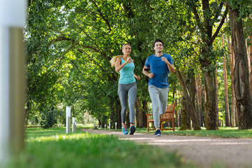 Sport culture. Happy fit couple doing cardio activities while jogging together in the park