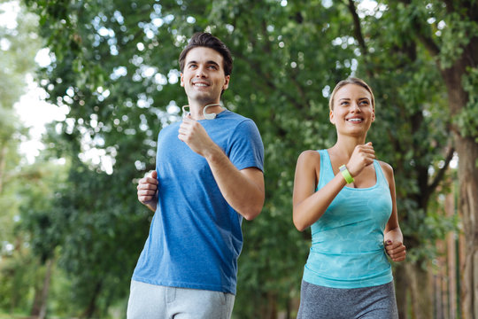 Healthy hobby. Delighted sportive couple smiling while enjoying sports activities together