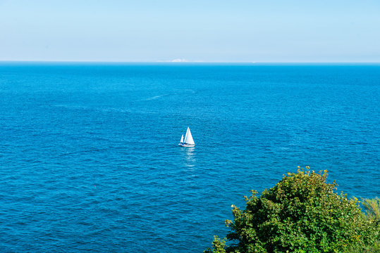 One Sailing yacht in еру ьшввду of brigh blue sea. Travel and active lifestyle concept. Selective focus. copy space.