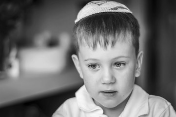A beautiful Caucasian kid with a traditional Jewish kippah cap on his head. A Russian-speaking Jew in Israel portrait. Post-Soviet Jews make up over 15 per cent of Israeli society. Black and white
