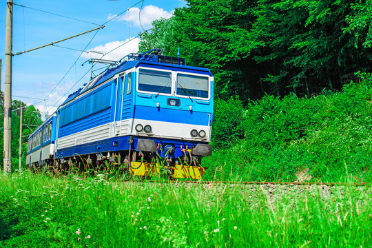 A blue electric locomotive passing the Czech countryside. A train running through the green valley. Rail transport in the Czech Republic