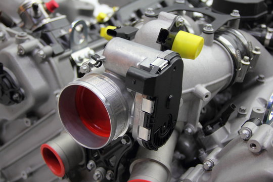 Model of new car V12 engine - throttle pipe with throttle position sensor and mass air flow sensor on motor block
