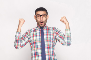 Happy winner handsome bearded businessman in checkered shirt, blue tie and black eyeglasses standing shouting and looking at camera with raised hands. indoor studio shot, isolated on grey background.