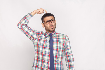 portrait of thoughtful handsome bearded businessman in colorful checkered shirt, blue tie and eyeglasses standing and looking away with funny face. indoor studio shot, isolated on grey background.