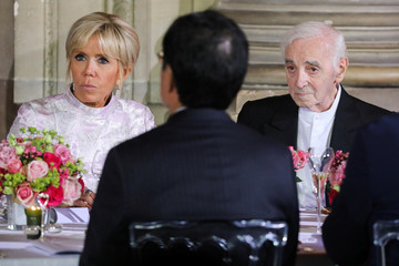 French President's wife Brigitte Macron and French singer Charles Aznavour listen to speeches at the start of an official state dinner with with Japan's Crown Prince Naruhito at the Chateau de Versailles castle