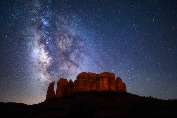 A meteor streaks through the Milky Way above Cathedral Rock in Sedona, Arizona.