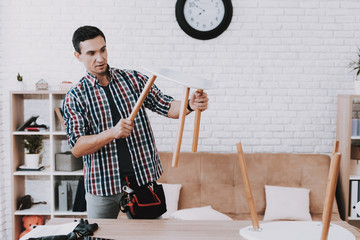 Young Man Assembling Coffee Table and Stools.