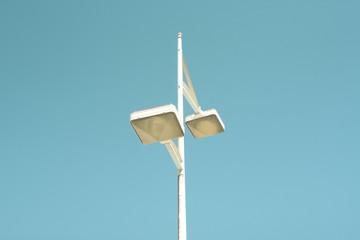 imagen minimalista de poste de luz callejero sobre un cielo azul despejado