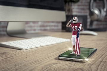 Football Player with a red uniform playing and coming out of a full screen phone on a wooden table.