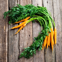 Raw carrot with green leaves on wooden background