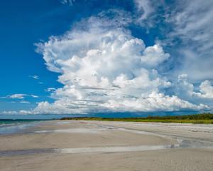 Growing cumulus cloud beyond the beach