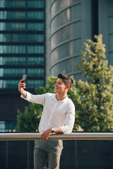 Young man with smartphone leaning on railing