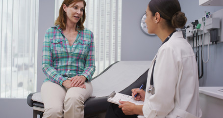 Lovely senior patient seated on medical chair while explaining to young latina doctor her health concern. Attractive mid aged woman consulting with young doctor about health condition