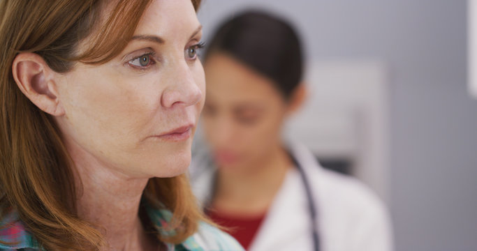 Closeup portrait of caucasian middle aged patient sitting in medical clinic waiting to consult with doctor. Tight shot of female patient waiting for doctor to examine her