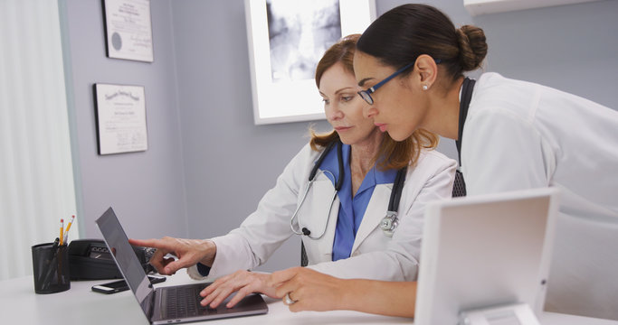Portrait of two medical physicians looking at lab results of patient on laptop computer. Close up of senior medical doctor discussing ct scans on computer with young colleague