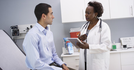 African senior medical doctor using high-tech elctronic notebook to take notes of patient. Portrait of young hispanic patient consulting with middle aged black doctor indoors medical clinic