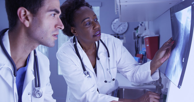 Senior African radiologist consulting with young Hispanic colleague over patient x rays. Two medical doctors reviewing patient x-ray of patients spine and skull