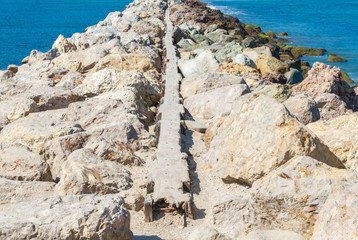 rocky breakwater in the Pacific ocean at Santa Barbara harbor with a narrow path on the top