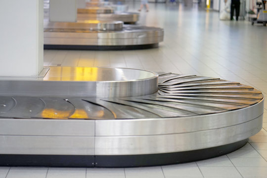 Empty airport baggage belt. Baggage claim area in the airport, abstract luggage line. Selective focus.